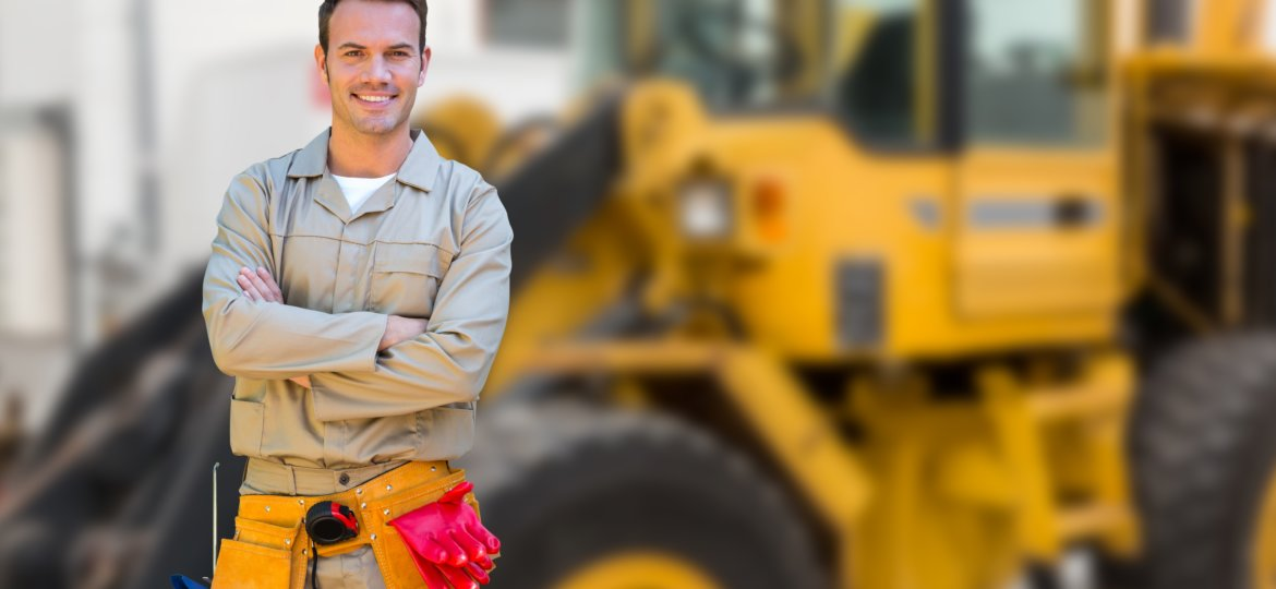 Worker standing with arms crossed against construction site in background